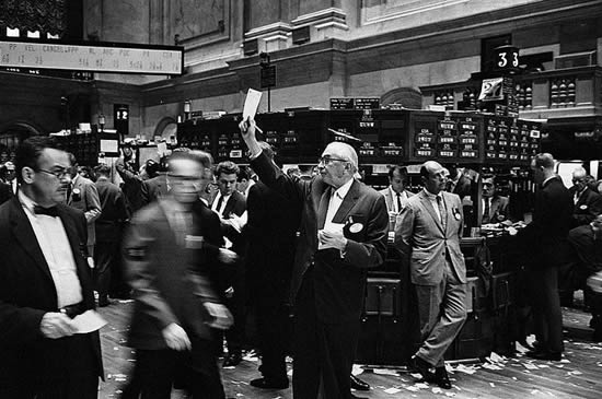 Photograph shows stock brokers working at the New York Stock Exchange.